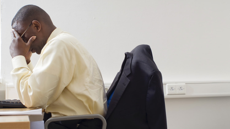 Mann mittleren Alters sitzt an seinem Schreibtisch, den Kopf in die aufgestützten Hände versunken