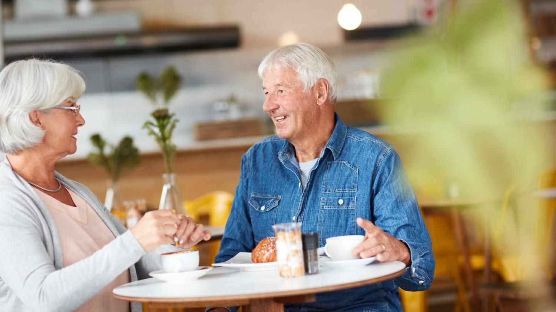 Älteres Paar unterhält sich angeregt in einem Café