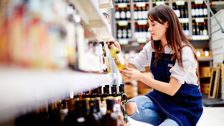 Eine junge Frau hockt in einem Supermarkt vor einem Regal in das Sie eine Flasche mit Öl einordnet