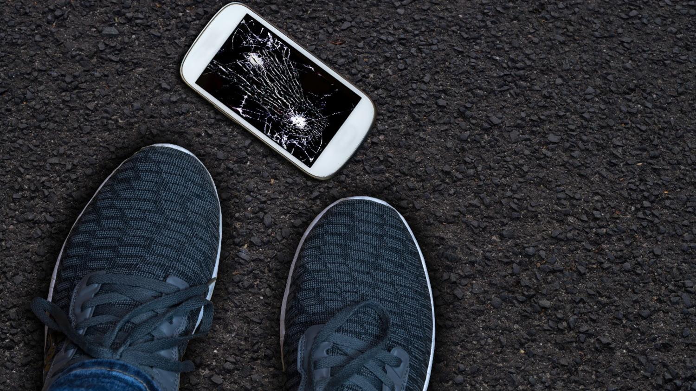 Ein Handy liegt kaputt auf der Straße