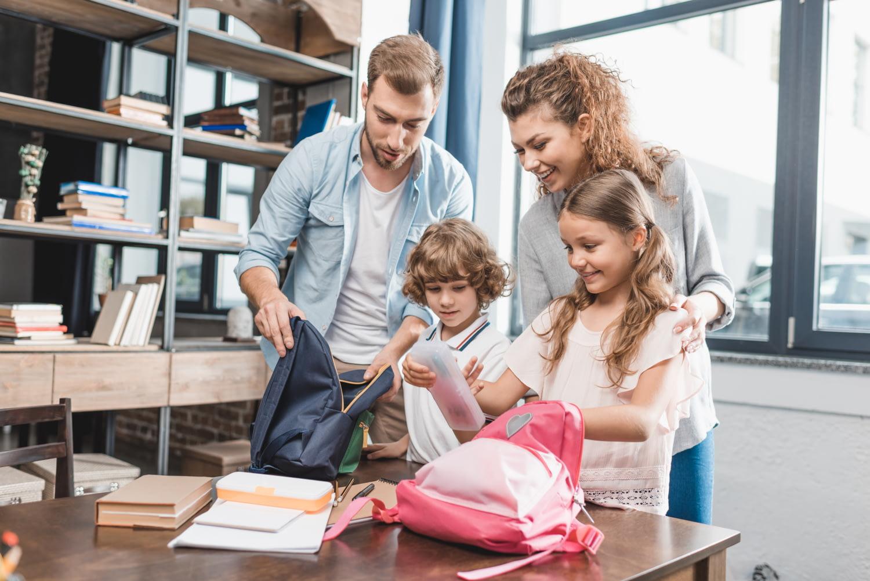 Elternpaar packt mit seinen zwei Kindern die Schulsachen