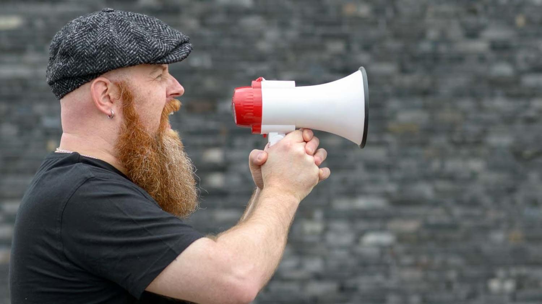 Bärtiger Mann steht vor einer Wand und schreit in ein Megafon