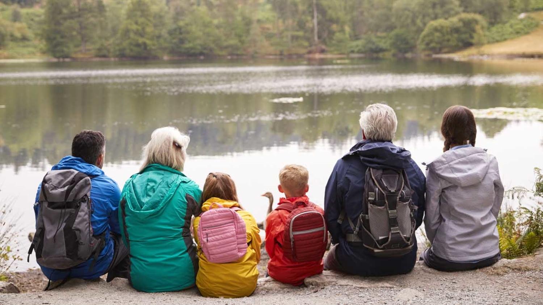 Drei Generationen einer Familie rasten bei einer Wanderung mit Blick auf einen See