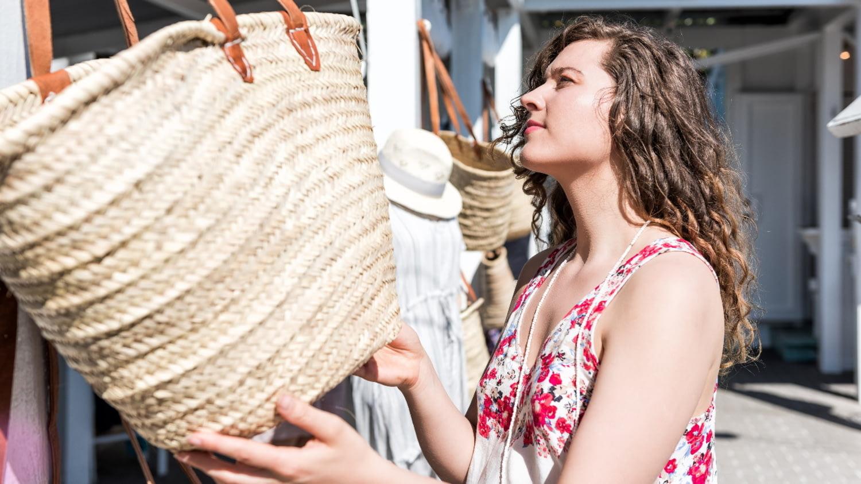 Junge Dame begutachtet Korbtasche beim Shoppingbummel