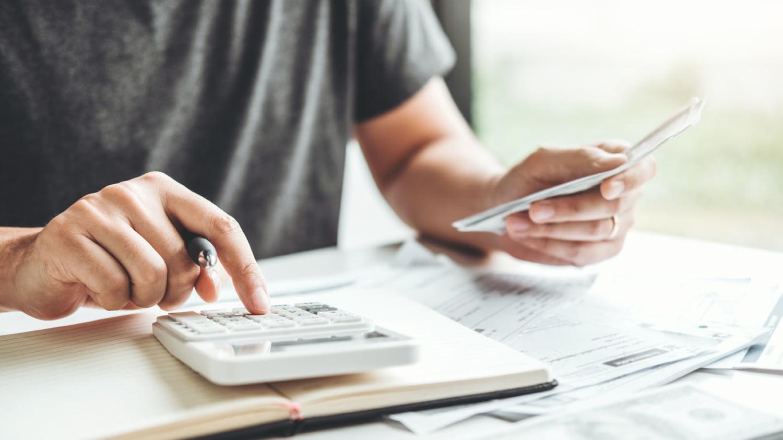 Mann nutzt einen Taschenrechner, um seine Einnahmen und Ausgaben zu berechnen