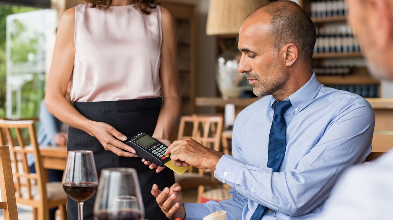 Ein Geschäftsmann zahlt im Restaurant mit der Kreditkarte und gibt dabei ein Trinkgeld