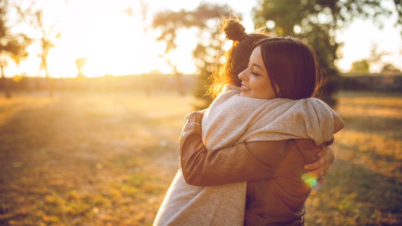 Zwei Frauen umarmen sich lächelnd