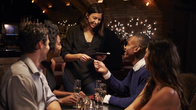Gruppe junger Leute zahlt im Restaurant mit Kreditkarte