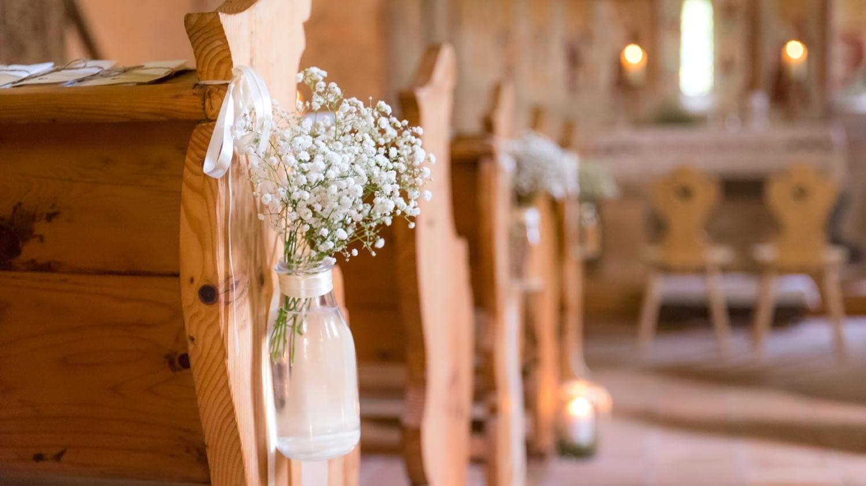 Romantisch mit Schleierkraut in kleinen Vasen dekorierte Kirchenbänke