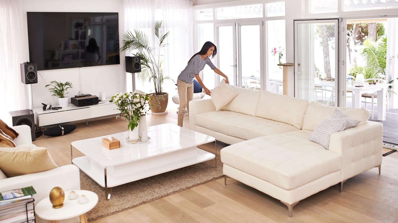 Eine Frau räumt in ihrem luxuriösen Wohnzimmer auf