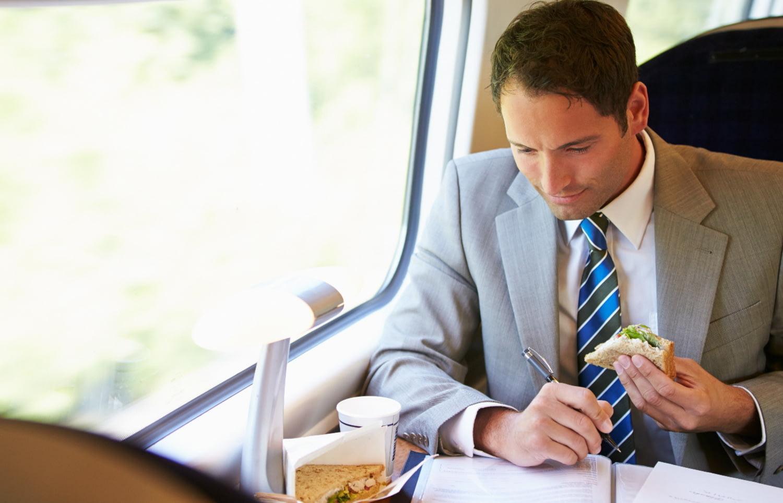 Im Zug reisender Geschäftsmann mit Snack guckt auf Dokumente