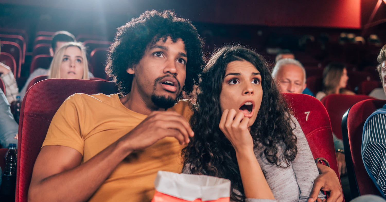 Junges Pärchen im Kino schaut erschrocken auf das Geschehen auf der Leinwand