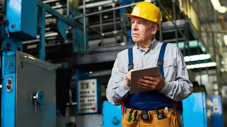 Älterer Arbeiter mit Helm und Blaumann steht mit einem Tablet in einer Maschinenhalle