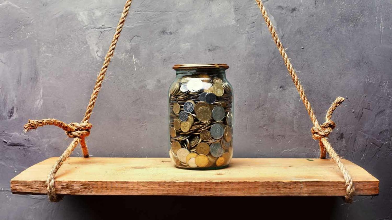 Ein Schraubglas voll mit Münzen steht auf einem Regalbrett, dass mit zwei Seilen in der Luft gehalten wird