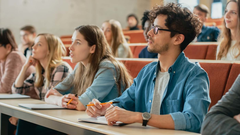 Eine Gruppe konzentriert zuhörender Studenten während einer Vorlesung im Hörsaal.