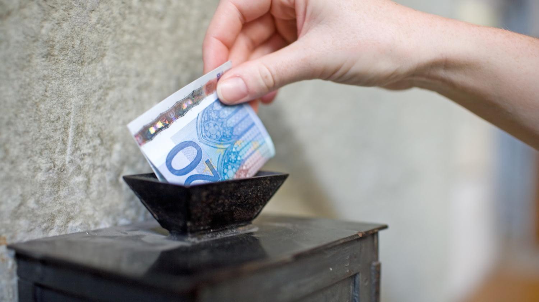 Hand in Großaufnahme, wie sie einen 20-Euro-Schein in eine Sammelbox am Kirchenausgang steckt