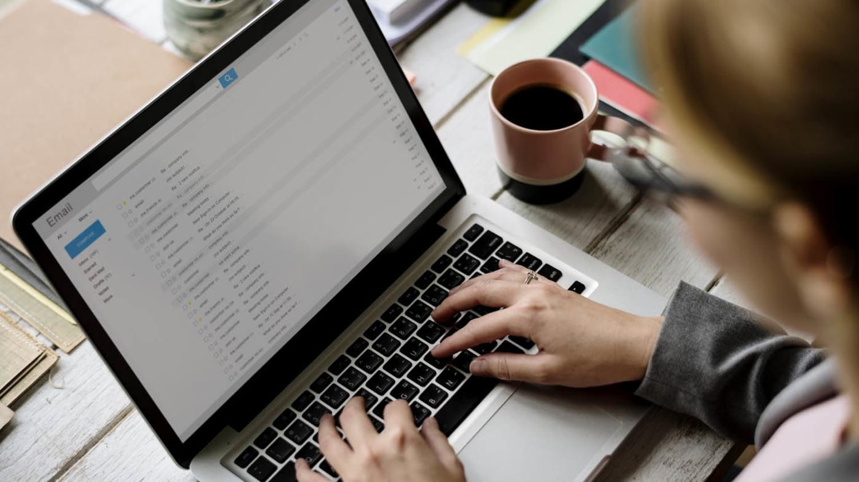 Geschäftsfrau prüft Ihr E-Mail-Postfach auf einem Laptop.