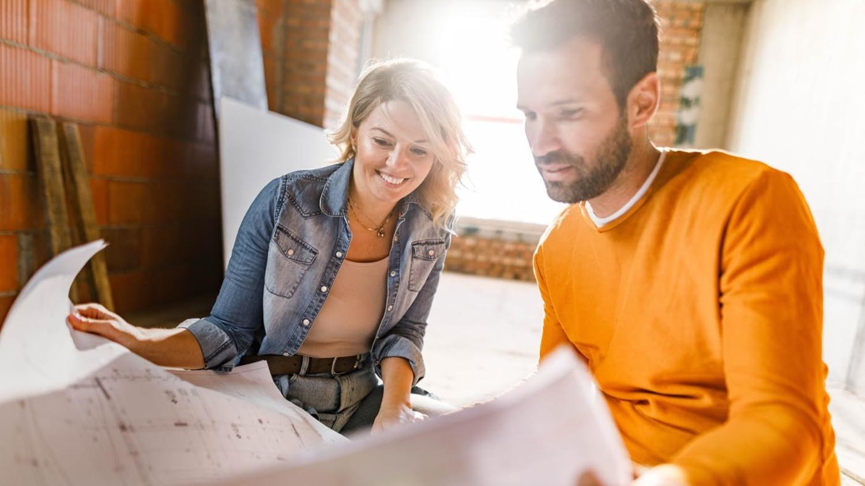 Junges Paar studiert Baupläne im Rohbau des eigenen Hauses