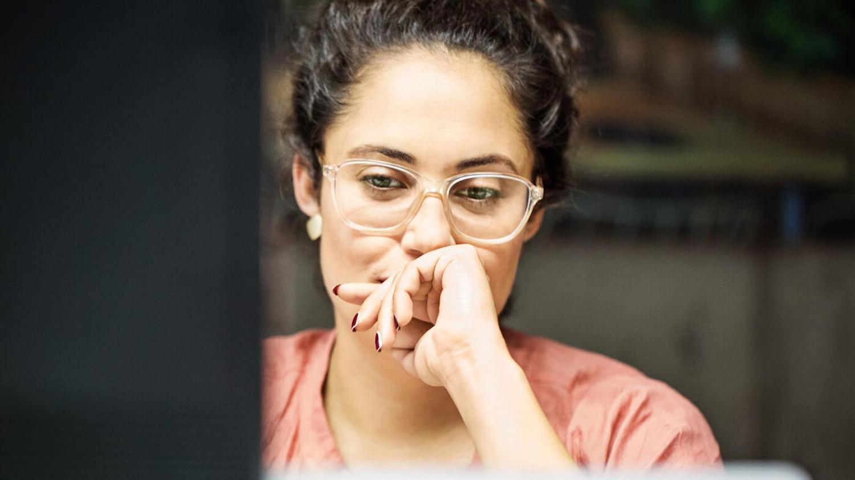 Frau blickt neugierig-skeptisch auf einen Computerbildschirm