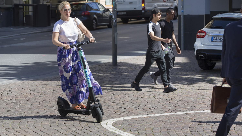 Junge Frau fährt auf einem E-Scooter durch eine deutsche Innenstadt