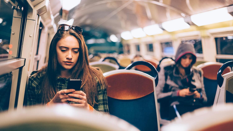 Junge Frau spielt auf dem Smartphone in der U-Bahn