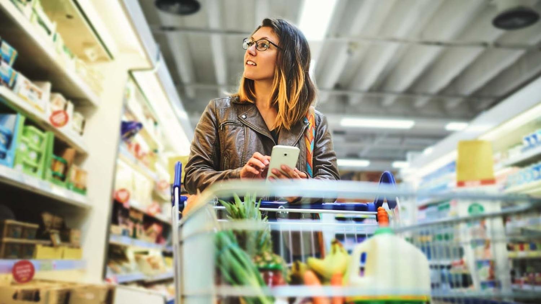 Junge Frau mit Einkaufswagen beim Lebensmitteleinkauf im Supermarkt