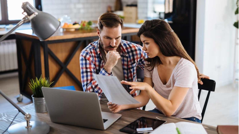 Frustriertes Paar überprüft Rechnungen zu Hause mit Laptop