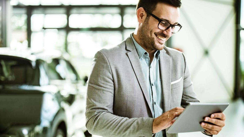 Ein gut gelaunter Verkäufer mit einem Tablet im Auto-Showroom