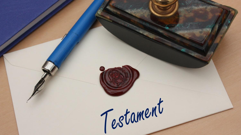 """Auf einem Tisch liegt ein versiegelter Umschlag mit der handschriftlichen Aufschrift """"Testament"""""""