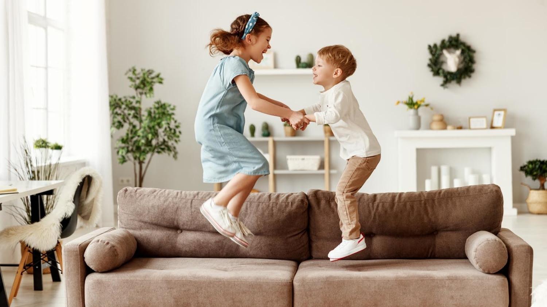 Geschwisterpärchen nutzt das Sofa im Wohnzimmer als Trampolin
