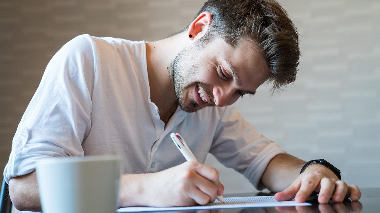 Ein junger Mann sitzt an einem Tisch und setzt lächelnd seine Unterschrift unter ein Dokument