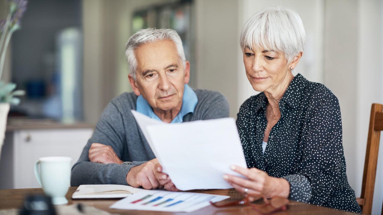 Ein älteres Ehepaar liest gemeinsam mehrere Unterlagen