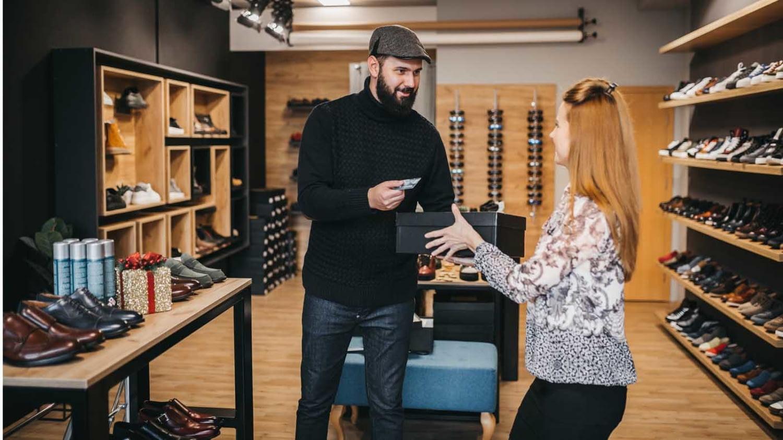Mann bezahlt mit Karte im Schuhgeschäft