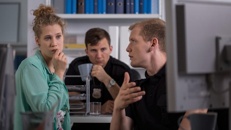 Besorgte junge Frau blickt auf den Bildschirm eines Polizeibeamten, der neben ihr sitzt