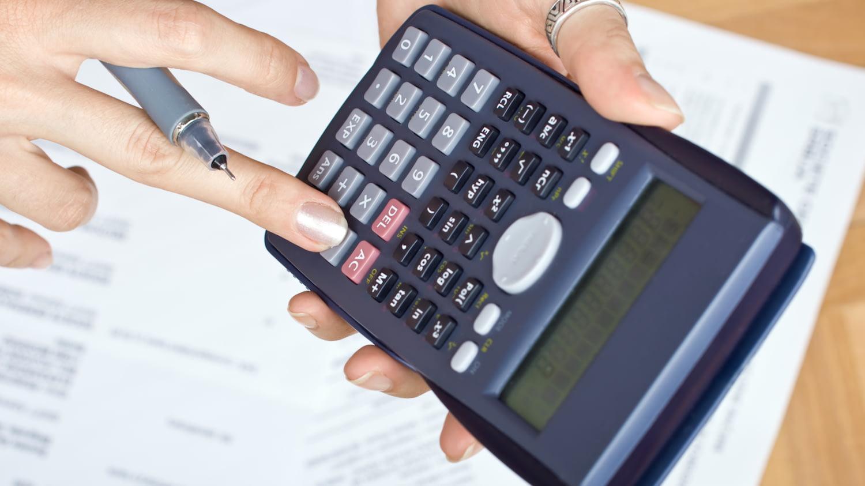 Betriebliche Altersvorsorge: Eine Frau berechnet die Kosten auf einem Taschenrechner.