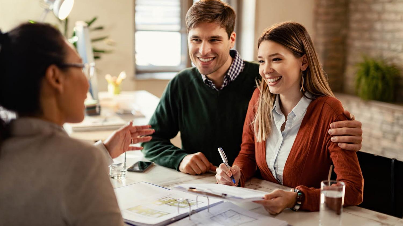 Ein junges Paar unterschreibt in einer Bankfiliale einen Kreditvertrag