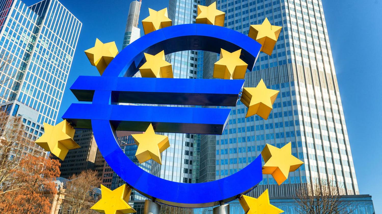 Eine stilisierte Euro-Skulptur mit zwölf Sternen vor dem Wolkenkratzer der EZB