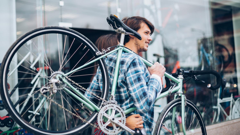 Mann trägt ein Fahrrad über der Schulter