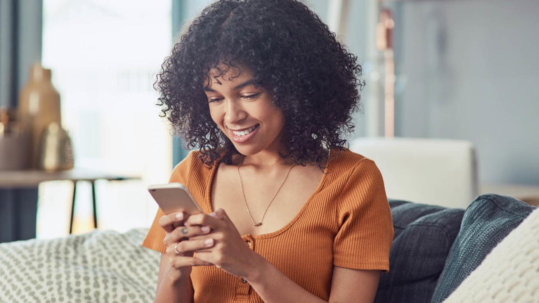 Junge Frau tippt lächelnd auf ihrem Handy