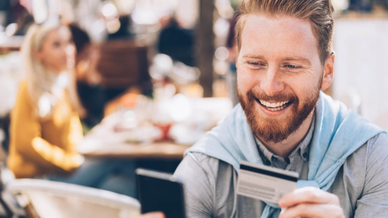 Mann blickt fröhlich auf sein Smartphone, in der Hand eine Kreditkarte