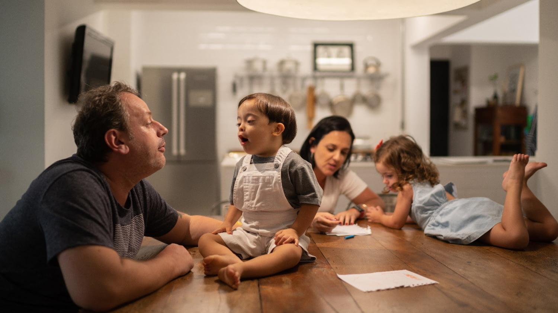 Eltern sitzen mit ihren Kindern am Tisch