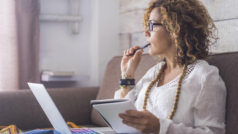 Eine Frau sitzt mit Computer auf dem Schoß und Notizheft in der Hand auf einem Sofa