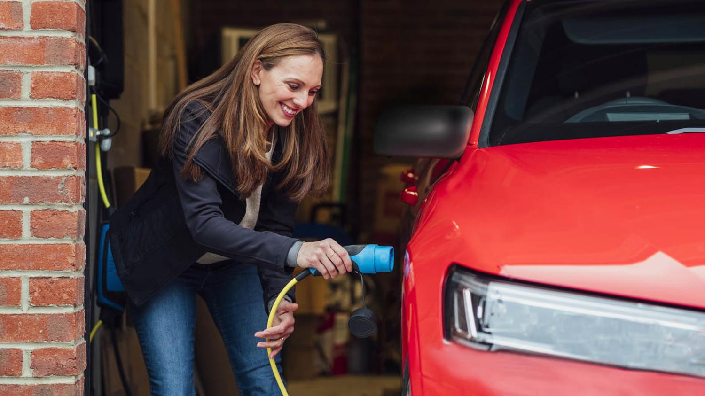 Frau schließt ein Elektroauto an eine Ladestation in ihrer Garage an