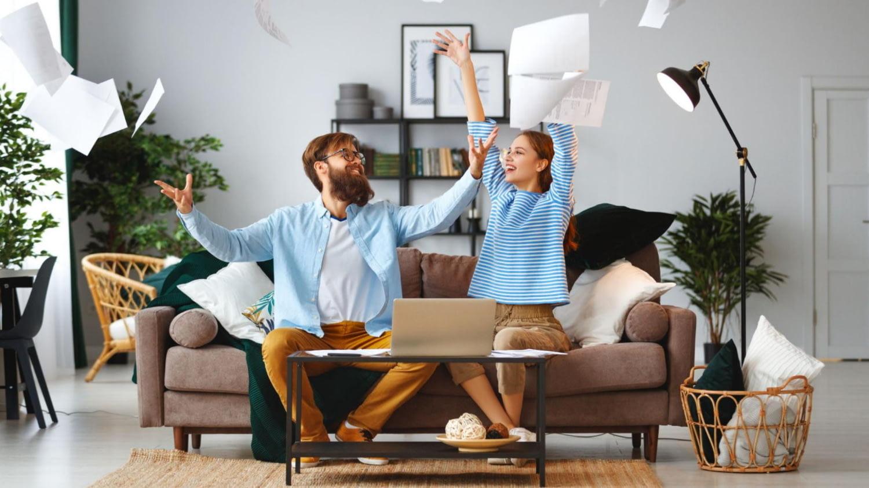 Glückliches Ehepaar sitzt auf dem Sofa und wirft seinen Kreditvertrag in die Luft