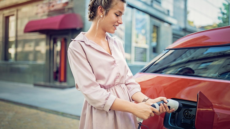 Junge Frau schließt ein Elektroauto an eine Ladesäule an