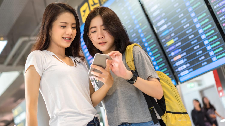 Zwei junge Frauen stehen am Flughafen vor einer Anzeigentafel und blicken gemeinsam auf ein Smartphone