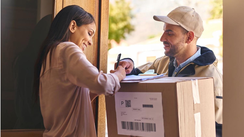 Ein Zusteller reicht einer Frau ein Paket an der Haustür