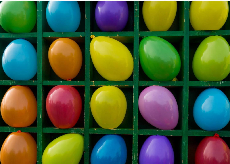 Wandregal mit mehreren offenen Fächern, in jedem ein aufgeblasener Luftballon