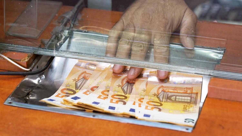 Hand schiebt mehrere 50-Euro-Scheine über einen Banktresen