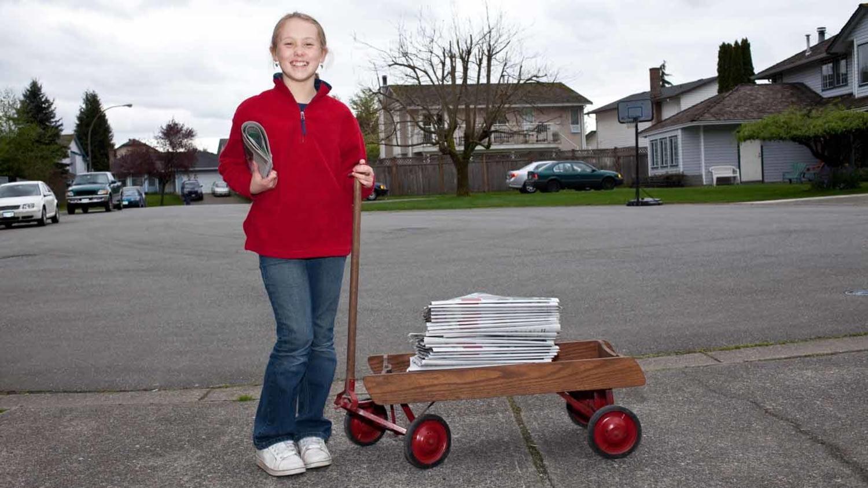 Ein Mädchen lehnt sich lächelnd an einen Bollerwagen mit einem Zeitungsstapel darauf